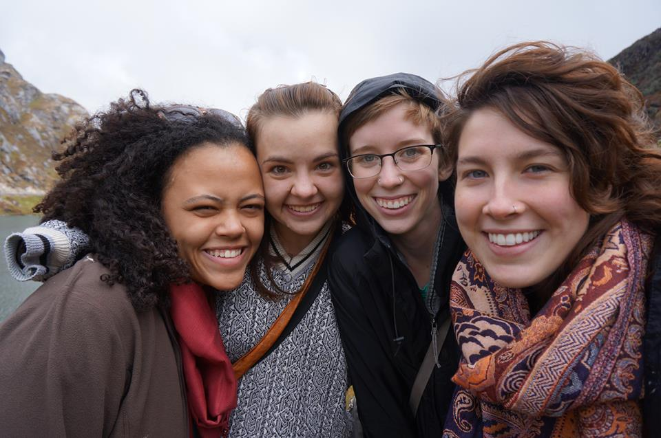 Four smiling female students near a mountain range and a body of water