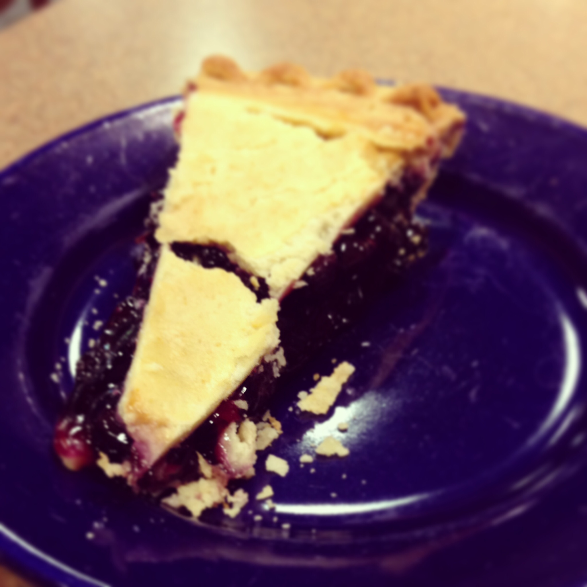 Blueberry pie slice on a blue plate