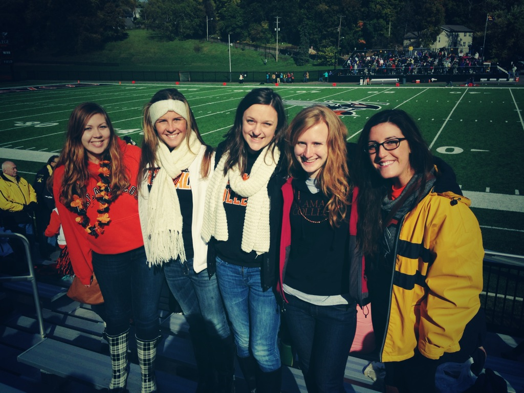 A group of college students dressing in spirit gear at a football game