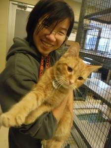 College student smiling and holding a cat