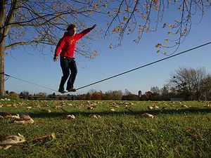 student walking on tightrope suspended in the air