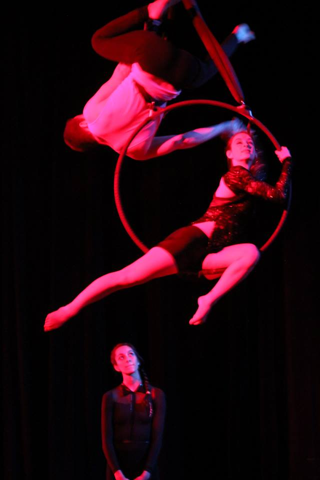 Three people in the middle of the acrobatic performance