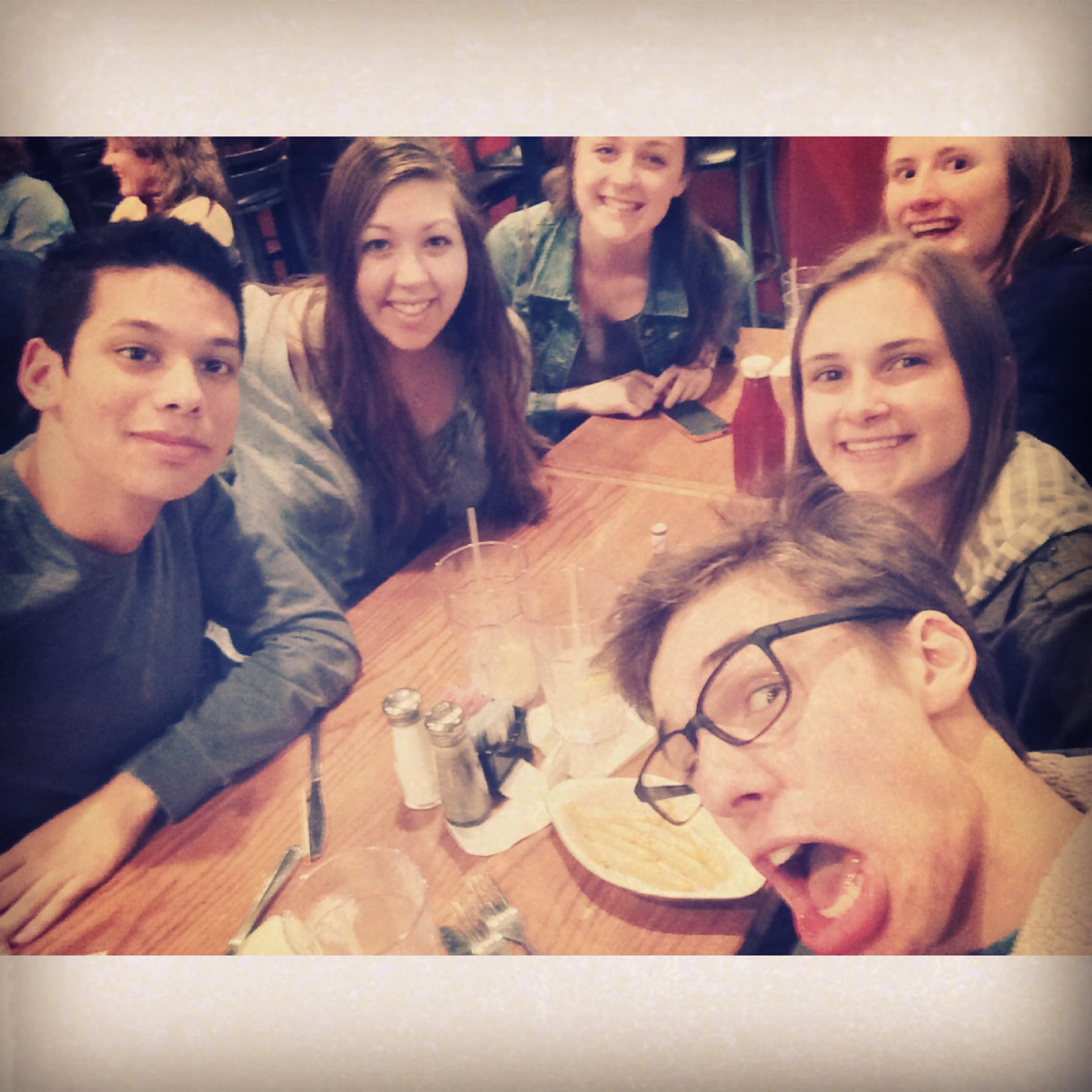 Six happy students in a selfie at a dinner table