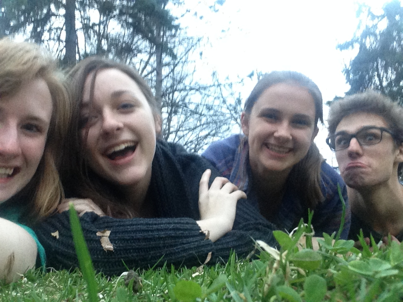 Four students lying in the grass in a selfie