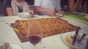 Students surrounding a large pastry with a glass of wine on the table