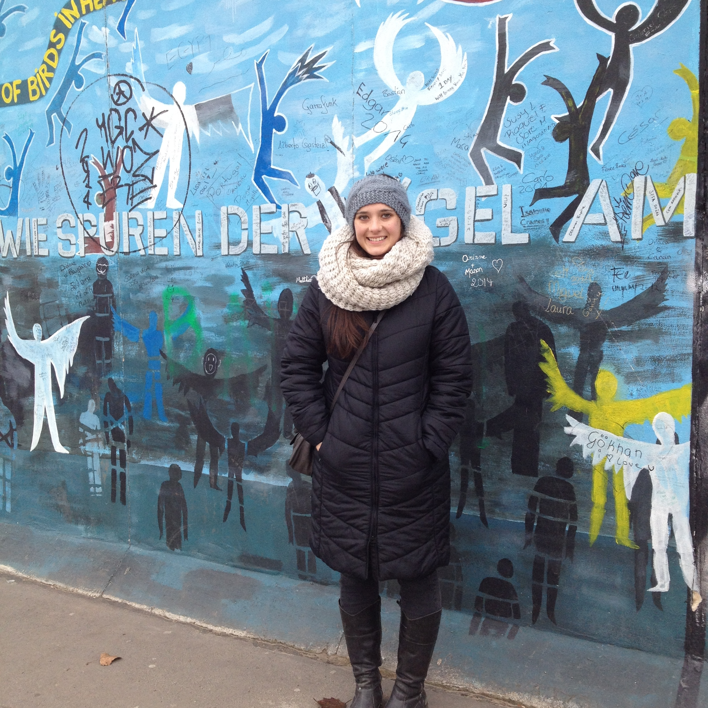 K student in front of the Berlin Wall