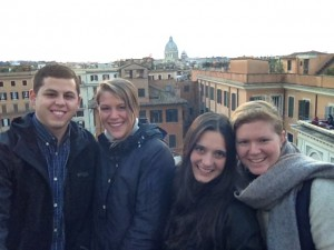 Four college students on top of stairs overlooking buildings