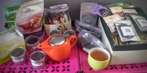 A collection of tea packets, a teapot, and a cup of brewed tea