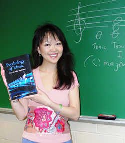 Kalamazoo College Psychology Professor Siu-Lan Tan holds her book in front of a blackboard