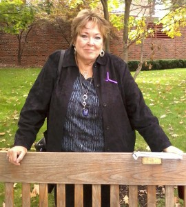 "Gail Griffin stands next to ""Maggie's Bench"" next to Stetson Chapel"