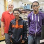 Two Kalamazoo College students and a professor standing in a lab