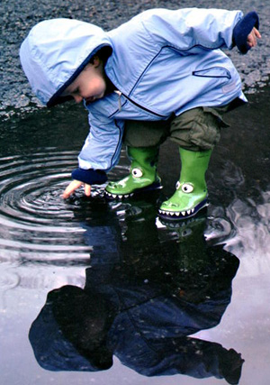 Young boy in rain gear splashes in puddles