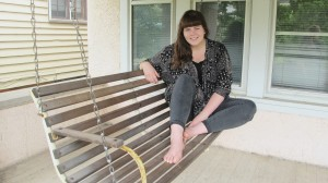 Haley Cartwright sits outside on a swinging bench