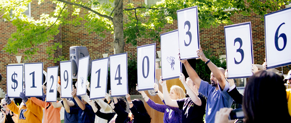 Participants in the Campaign for Kalamazoo College hold up signs indicating $129,140,336 was raised