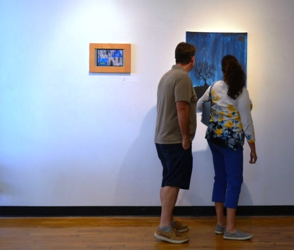 Art Hop attendees view a painting from an ARTifact participant