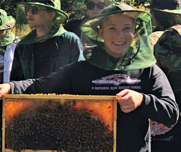 Student-Holding-a-Honey-Bee-Hive-Frame