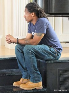 side profile of David Stovall sitting at the edge of a stage