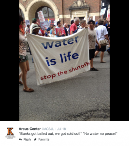 """Arcus Center instagram post on protest where a banner reads, """"water is life stop the shutoffs"""""""