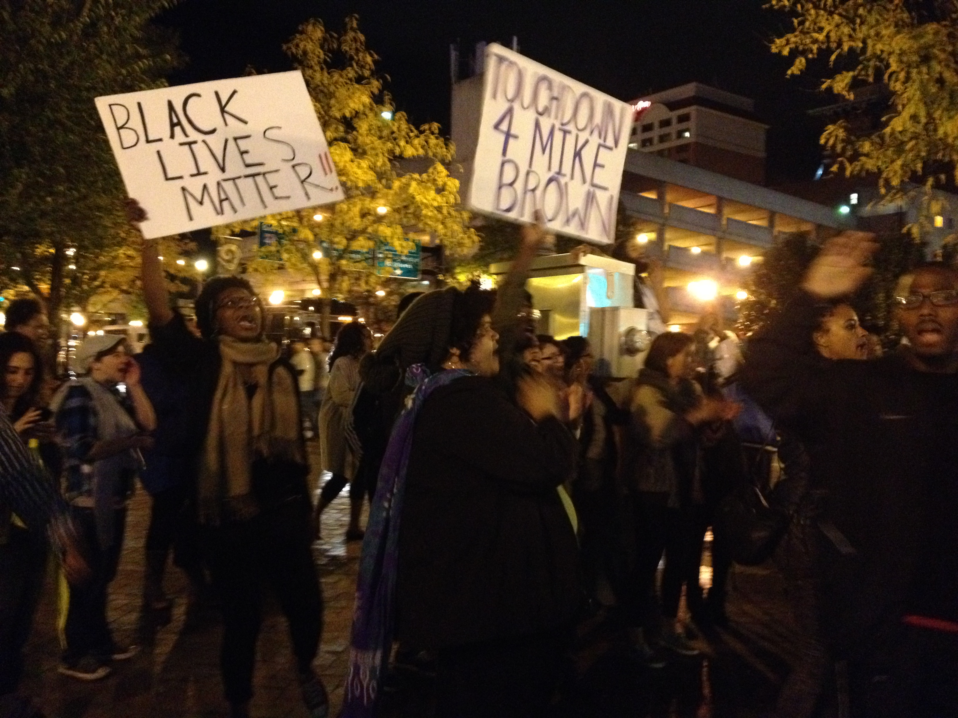 """Rams Game Protest at night with signs that read, """"BLACK LIVES MATTER and touch down for Mike Brown"""""""