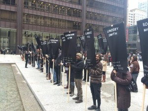 people stand side by side holding black banners with the names of those tortured in white letters