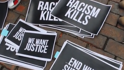 """stacks of antiracist posters and signs that say """"racism kills"""" ad """"we want justice"""""""