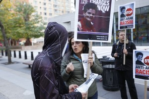 """Protestors in New York hold signs with Rasmea Odeh's face and text reading, """"Stop anti-arab racism"""""""