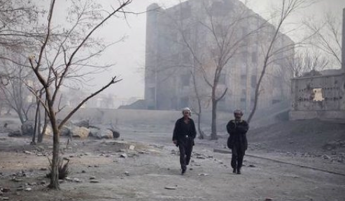 two people walking down a deserted street with smoke and rubble