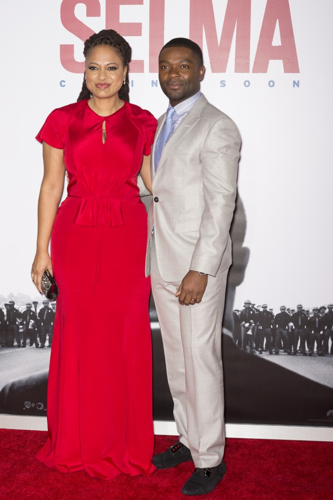 director Ava DuVernay and actor David Oyelowo standing together in front of Selma movie poster
