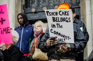 """protestor sign that reads, """"Psych care belongs in the community not jail."""""""