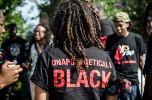 """the back of a black person with dreads and shirt that reads, """"Unapologetically BLACK"""""""