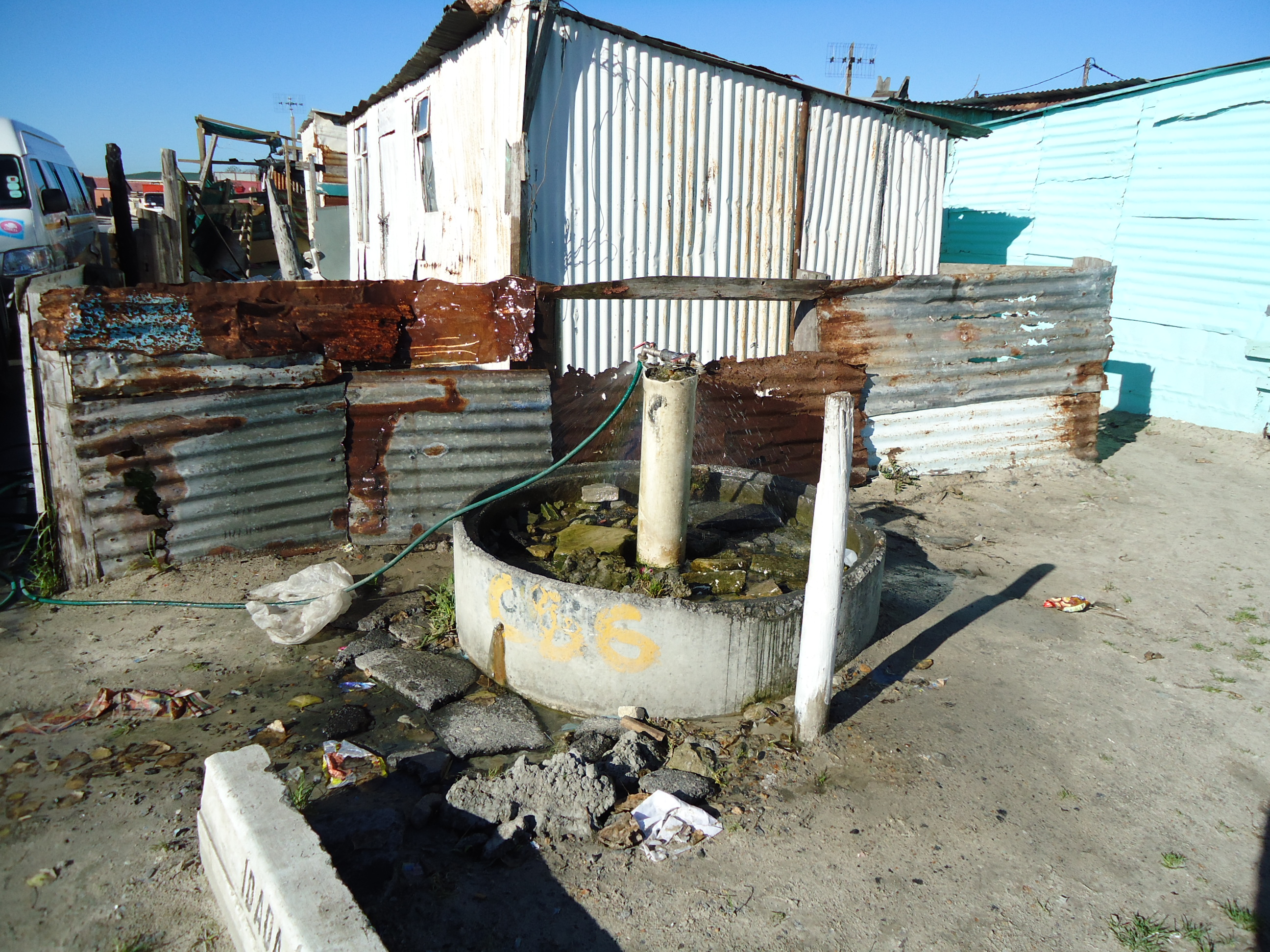 exposed pipe out of the ground as Communal water tap in Cape Town slum