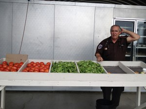 A police officer oversees incarcerated men selling vegetables at a produce stand.