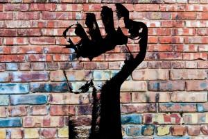 illustrated black graffitti raised fist onto brick wall with faded past graffitti.