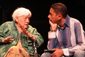 Grace Lee Boggs talking to Robin D.G. Kelley while he listens attentively.
