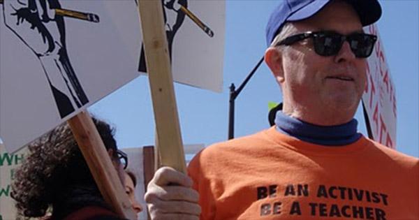 "Protestor wearing a shirt that states, ""Be an Activist. Be a teacher."""