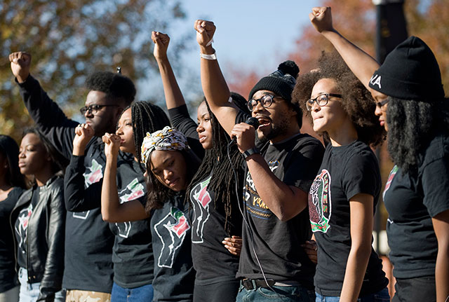 Students protesting and raising the black fist