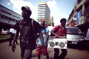 Three Ugandan people walking in the street with a boombox