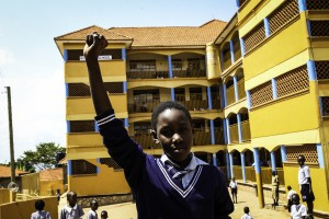 Ugandan student in school uniform with fist in the air