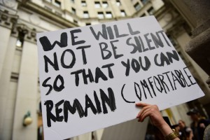 "protest sign with text reading ""We will not be silent so that you can remain comfortable."""