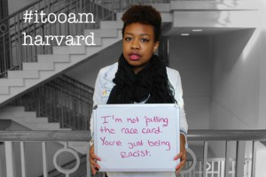 "black student with a sign saying, ""I'm not pulling the race card. You're just being racist."""