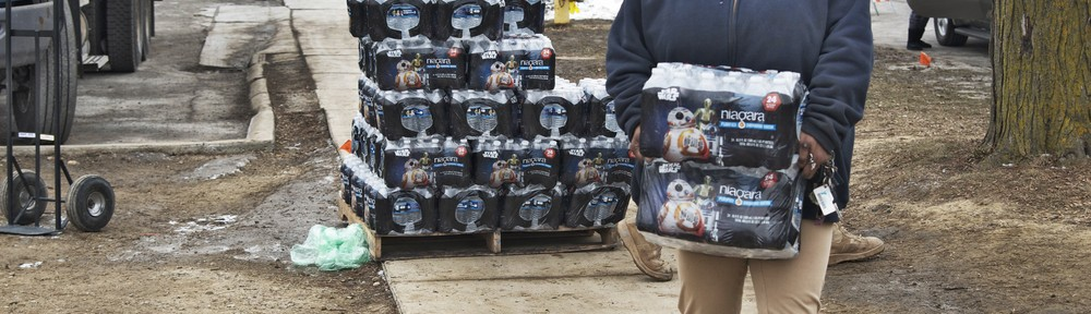 person walking and carrying a pack of water from a large stack of water bottles