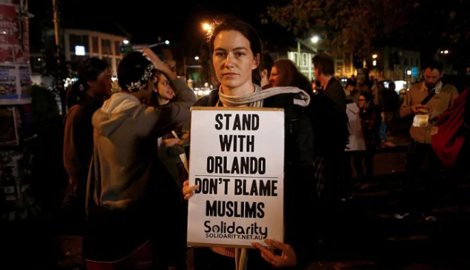 "protester with sign that reads ""stand with Orlando. Don't blame Muslims"""