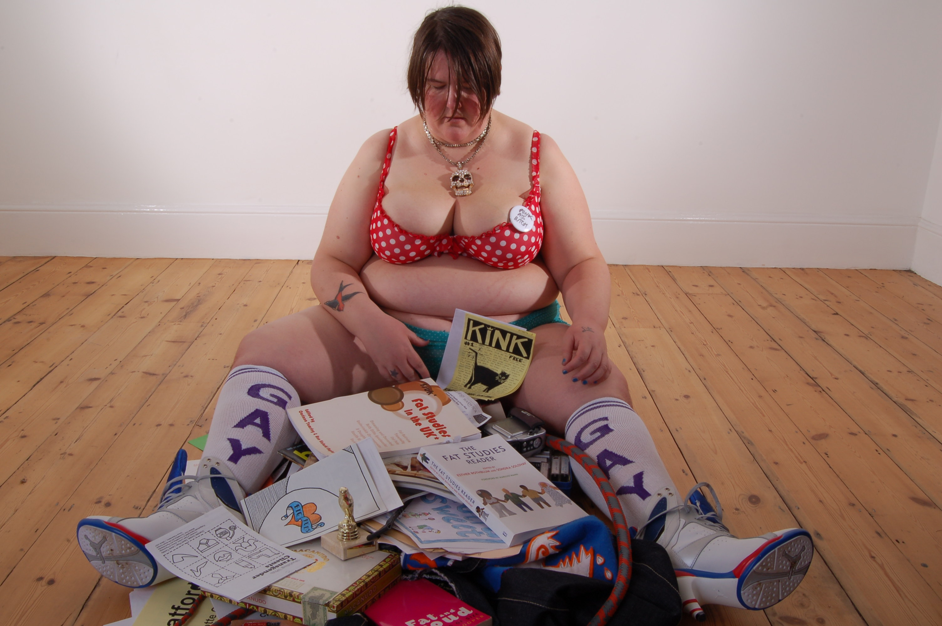 Charlotte Cooper sitting on the floor with books and magazines surrounding her
