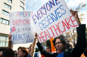 """Protestors marching with signs that read """"in America Everyone deserves Health Care"""" and """"Everyone Deserves HealthCare"""""""