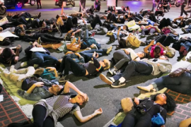 "a large group of protesters laying on ground during a ""die-in"""