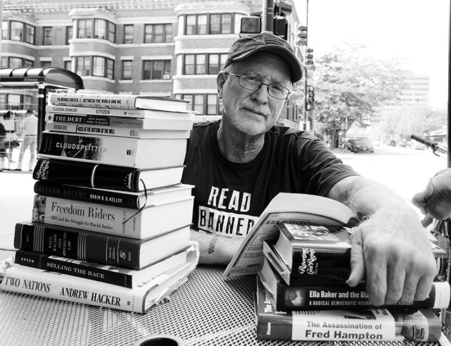 Bill Ayers sitting at a table with a pile of books