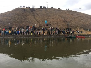 """Turtle Island"" is a sacred burial ground and site for many actions against DaPL. Note the military presence at the top of the hill. Photo credit: Keedra Gibba"