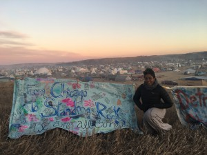 The author with a banner created by Chicago's For the People's Artists Collective. Behind her is the Ocheti Sakowin encampment. The big white dome tent is where she and others met and discussed solidarity. The banner faces out to Highway 1806. Photo credit: Sarai Bernice