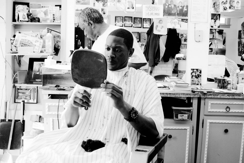 african american male looking at his new hair cut in a handheld mirror