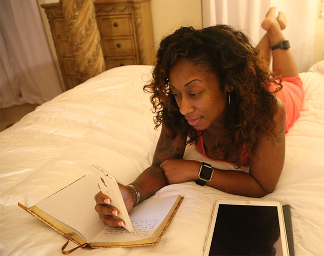 Marissa Alexander wearing an ankle monitor laying on a bed with a book, a phone, and a tablet